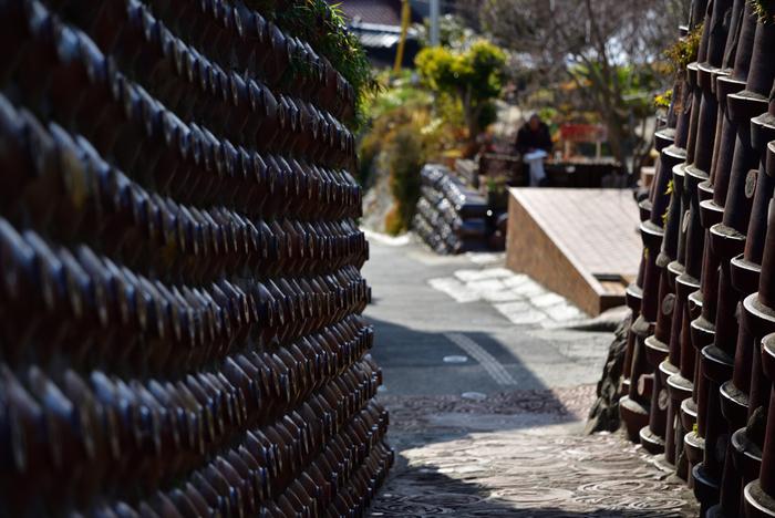 明治期に作られた土管と昭和初期に作られた焼酎瓶おおわれた「土管坂」の壁面は圧巻です!よ~く見ると、地面にも焼き物が敷き詰められています。これは土管の焼成時に使った捨て輪「ケサワ」の廃材で、滑らず歩きやすいようにとの配慮だそうですよ。