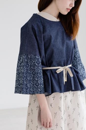「rikolekt(リコレクト)」の袖コンシャストップスは、フレアスリーブの裾に花の輪郭が並べられたシックなデザイン。袖だけでなくウエスト周りもフレアデザインになっているので、ゆったりと着こなすことができます。付属の麻ひもでブラウジングも可能で、トップスのシルエットを自由に変えられるのも魅力的。