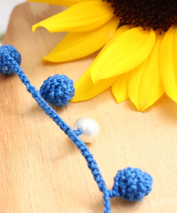 キュートな印象の中に、柔らかさや温かさを感じられるかぎ針編みのネックレス。軽くて扱いやすいコットンパールを組み合わせていることで、程よいカジュアル感を演出できています。