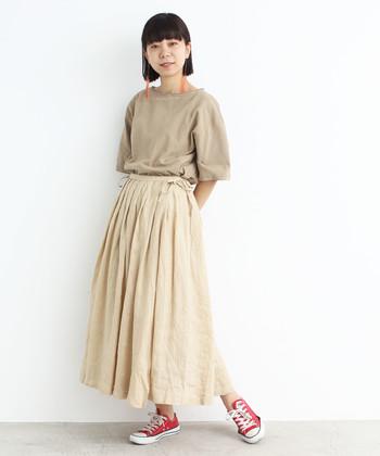 ベージュのTシャツとフレアスカートで、飾らないリラクシースタイルに。ぼんやりとしたイメージにならないよう、足元には鮮やかなレッドを乗せて。