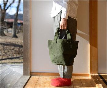 スニーカー作りなどに用いられるヴァルカナイズをコットンに施し、完全防水のクロスでバッグを作りました。タフな扱いにも耐えてくれる丈夫なバッグです。