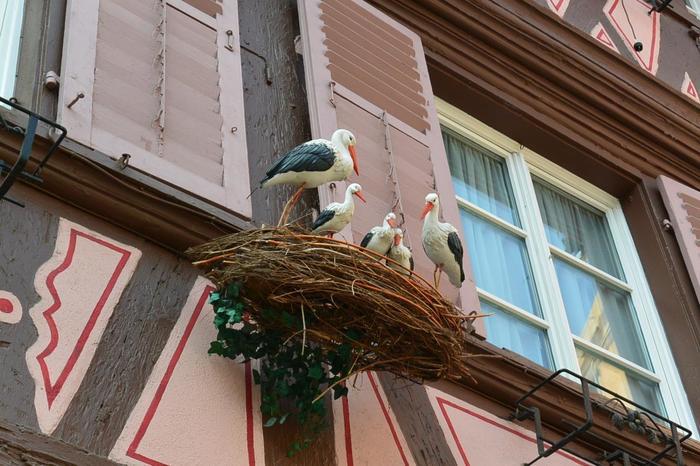 """アルザス地方では""""幸せを運ぶ鳥""""と言われるコウノトリがシンボルとして使われており、町のいたるところに装飾品として飾られていたり看板に施されていたり、はたまたお土産屋さんにはかわいらしいマスコットも沢山売られています。あちこちで発見できるので探してみるのもおもしろいかも。"""