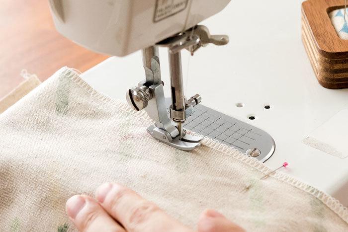 三つ折りを一度開き、上から8cmあけたところから1cmの縫い代をとって2枚を縫いあわせます。この時、2枚の布がずれないように、まち針で固定します。