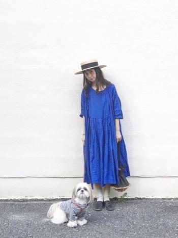 """色鮮やかなブルーのロングワンピースとカンカン帽の組み合わせ。ハットのリボンとバッグのカラーを""""黒""""でリンクさせることで、夏のお嬢さんスタイルをシックに引き締めています。"""