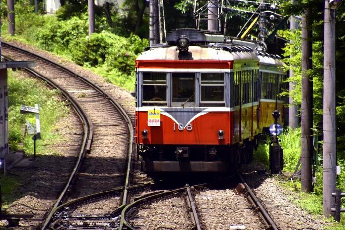 """箱根登山電車は、小田原と強羅を結ぶ、大正8年開通の日本で唯一つの山岳鉄道です。  急勾配を駆け上り、トンネルをくぐり、渓谷に架けられた幾つもの鉄橋を走りぬけます。車窓には、豊かな緑や花々、涼やかな清流といった素晴らしい風景が流れていきます。  【上大平台信号所でスイッチバック中の「箱根登山電車」。鉄道ファンでなくても楽しいのが、箱根登山電車の名物""""スイッチバック""""。高低差のある線路を往く登山電車では、3回のスイッチバックを行う。】"""
