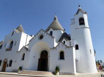 """旧市街にある""""サンタントニオ教会""""はトゥルッリ屋根の唯一の教会。白い壁と青い空のコントラストが美しいです。"""