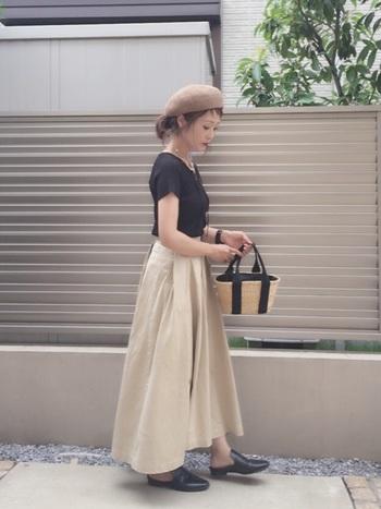 ペーパー素材のベレー帽に、黒のTシャツとベージュのロングスカートを合わせたスタイリング。小さめのカゴバッグをプラスして、ベージュ×黒で作ったプレーンなコーデです。ペーパーハットが難しいと感じる方は、全体のカラーバランスを帽子に合わせるのもおすすめ。