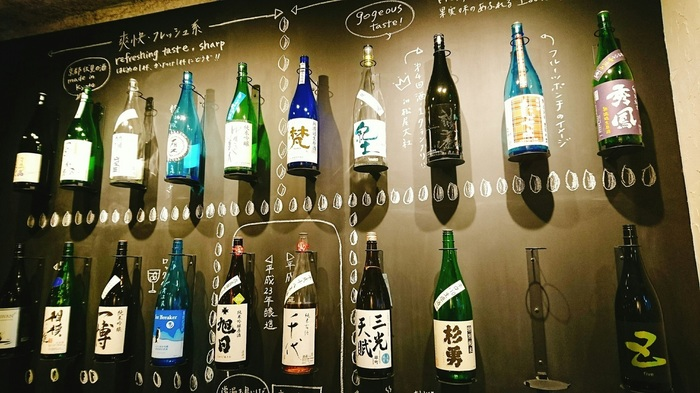 店内に入ってびっくり。壁には、そんな目利きの店主によって選び抜かれた日本酒たちがズラリと並べられています。しかも味を想像しやすいように分かりやすい説明付き。見た目のお洒落さに、写真撮影されるお客様も後をたたないのだとか。