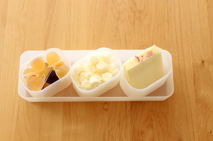 ミニサイズのゼリーやチーズなど、袋からいちいち出すのが面倒だったり、包装袋そのものがかさばって整理が難しい食品は、一旦小さなケースにまとめ、それをさらに引き出しやすい大きなケースにINしておくのも一つのアイデアです。チーズ類は乾燥しやすいので長期保存には向かないそうですが、小袋入りのわさびやお醤油などの整理にも良さそうな方法ですね。