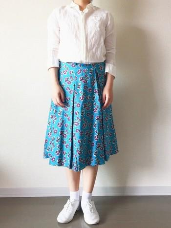 パッと目を惹く華やかな花柄のミモレスカートは、他のアイテムをホワイトでシンプルにまとめて着こなすのがオススメ。鮮やかなブルーとホワイトの対比が夏らしく、清楚な大人の着こなしになります。