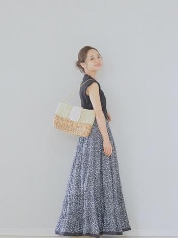 細かい花柄のロングフレアースカートは清楚な印象を与えます。トップスは黒のノースリーブですっきりと、かごバッグで夏らしさを添えて♪