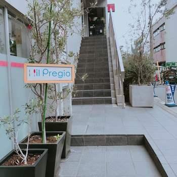 「イルプレージョ」はシンプルなコンクリートの建物の2Fにある、イタリアンレストラン。1Fの入り口にあるこの札が目印。