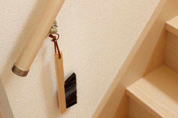 階段の登り口の手すり部分にフックを取付け、ブラシを掛けておくと便利。階段掃除のときにも、廊下の巾木掃除をするときにもサッと掃除がしやすい。