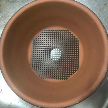 ①鉢の底にある穴の上に、ネットを敷きます。