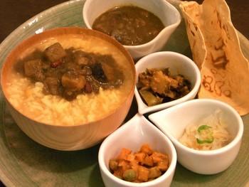 ネパールお粥定食。セットのおかずをお粥の上に少しずつ乗せて、味の変化を楽しみます。