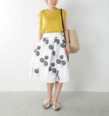 白地に黒の花が描かれたモノトーンのスカートは、少し大きめの柄でもシンプルに着こなせます。明るいマスタードカラーのトップスとシルバーのサンダルで、夏らしい季節感をプラスしています。