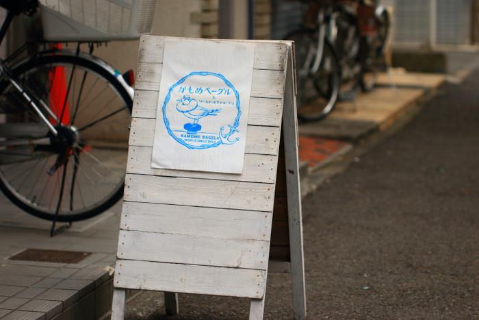 JR根岸線の石川町駅北口から徒歩2分、横浜市営地下鉄の関内駅からは徒歩5分。天然酵母のベーグルとプチパン、惣菜パンなどのテイクアウト専門店「かもめベーグルラボ」は、華やかな元町商店街から少し離れた路地にあります。「横浜=港町」「かもめ」「ベーグル」のモチーフから生まれたちょっぴりシュールなロゴは、イラストレーター・テキスタイルデザイナーのアニャンさんが手掛けたもの。