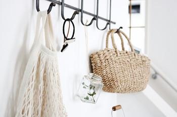 収納をかごやネットに変えるだけで、お部屋の夏らしさはぐっと高まります。壁に取り付けたフックに、かごバッグとネットのバッグを。小物などをさっとしまうのにも便利!