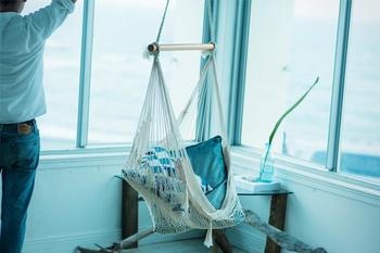 天井からハンモックのように吊るしたネットには、クッションなどのアイテムを。無造作に詰め込んだだけなのに、おしゃれでさわやかな印象に。