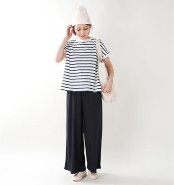 黒のイージーパンツを、ボーダーTシャツと合わせたスタイリングです。シューズとバッグとニット帽を白で合わせ、シンプルラフなコーディネートに。ニット帽はIラインを強調して着痩せ見えする効果も期待できるので、夏でも涼しい素材のものを選ぶのがおすすめです。