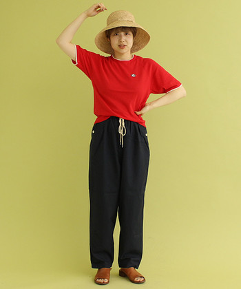 ネイビーのイージーパンツに、赤のTシャツを合わせたコーディネートです。キュートな印象のストローハットや、サンダルを合わせてリラックス感のあるスタイリングに。ウエストの紐をさりげなく見せつつタックインすることで、ラフになり過ぎない着こなしに仕上げています。