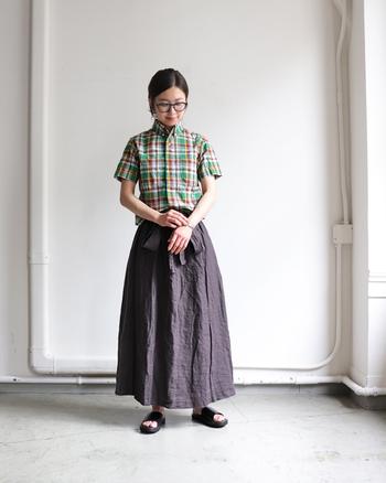 グリーンやイエローのカラーが映える半袖チェックシャツに、グレーのロングスカートを合わせたコーディネートです。色々なカラーが使われているトップスには、落ち着いたカラーのボトムスを合わせるとチェックが浮かずに大人っぽい着こなしに仕上がります。