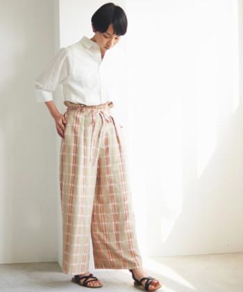 リネン素材のチェック柄パンツは、女性らしいナチュラルカラーが印象的なアイテムです。ちょっぴりガーリーになりやすいデザインでもあるので、白シャツやブラウスなどのシンプルな大人アイテムとスタイリングするのがおすすめ。