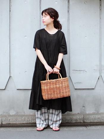 黒のワンピースの裾から、さりげなく見せたチェック柄のワイドパンツが印象的な着こなしです。チェック柄は面積が広くなる程着こなしが難しくなるアイテムでもあるので、シンプルな黒ワンピースからちょっとだけ覗かせるスタイリングはバランス感が抜群です。