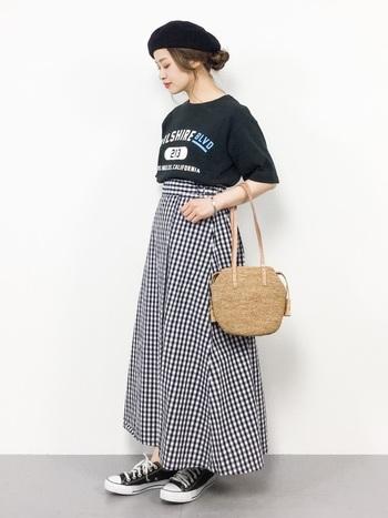 チェック柄のハイウエストロングスカートは、黒のロゴTシャツと合わせてほんのりカジュアルに。トップスだけでなくベレー帽やスニーカーなど、全体をモノトーンでまとめて柄スカートをシックに着こなしています。