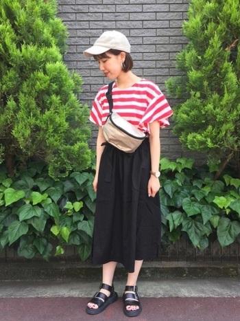 赤ボーダーのトップスを、黒のロングスカートに合わせたカジュアルなコーディネートです。白の帽子や黒のサンダルを合わせて、シンプルなマリン風コーデに。