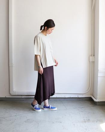 女性らしいとろみスカートは、ゆったりTシャツで今どきにスタイリング。仕上げは空色のスニーカーで、褐色コーディネートを夏っぽく味つけして。