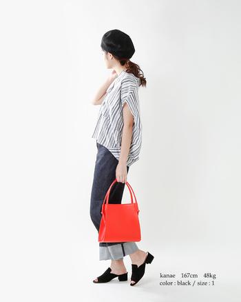 スマートなストライプブラウスが、ゆとりのあるサイジングで柔和な表情にシフト。オレンジのバッグで、手元にはウォーミーな華やかさを。