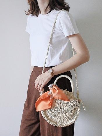 シンプルな丸型ミニカゴバッグには、差し色として明るめのスカーフを巻いて夏らしさを添えるのもいいですね。薄手のスカーフ素材が涼しげな印象で大人の上品さを演出します。