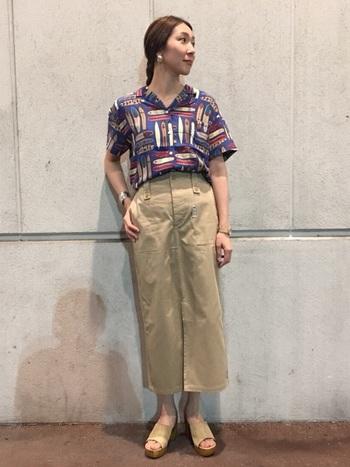 レトロな色合いのサーフ柄のアロハシャツとワークテイストのタイトスカートを合わせたカジュアルスタイル。ボトムとサンダルをベージュカラーで品良くまとめています。