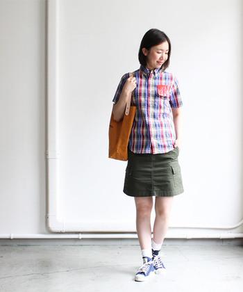 鮮やかなマドラスチェックのシャツ。その色どりが映えるよう、スカートにはシックなカーキを選んで。大きめのフラップポケットつきなら、ほんのりワーク風のテイストに!