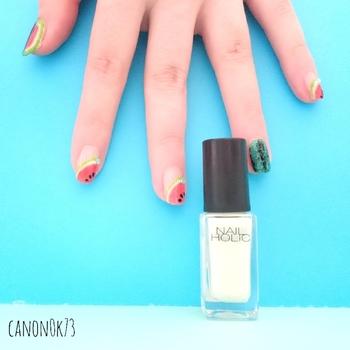 スイカを斜めに描いてリズミカルな指先に。薬指には、スイカの皮をイメージした深いグリーンをオン!表面のしま模様も丁寧にスケッチして。