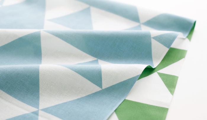 薫風(くんぷう)とは初夏の季語。生命力あふれる青々とした葉の香りを運ぶ風を表現しています。弥生時代の銅鐘や土器などにも見られる鱗模様をモダンにアレンジした柄です。