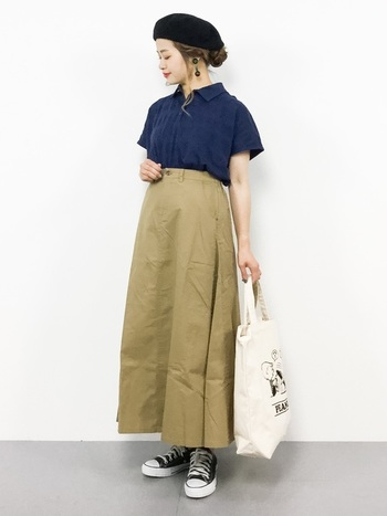 ネイビーのポロシャツは馴染みの良いベージュのスカートを合わせてベーシックに。定番コーデはヘアスタイルを女性らしくまとめつつ、トートバッグとスニーカーで外してメリハリを出すと◎。