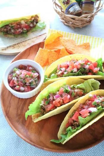 メキシコ料理の代表格「タコス」。トウモロコシからできた「トルティーヤ」と言われる生地に、サルサやタコスミートなどの具材をのっけて食べるお料理です。  こちらのレシピは、合いびき肉をチリパウダーでスパイシーに炒めたタコスミートと紫玉ねぎやトマトなどの彩り野菜を爽やかに漬け込んだサルサをトッピング。ハラペーニョをかけてホットに仕上げて♪