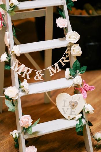 木製のアンティーク感漂う脚立に、お気に入りの小花とロゴガーランドをあしらって、会場の目につく場所にセッティング。こうしたゲスト用のフォトブースも用意しておくと、ゲストにも楽しんでもらえるしより華やかな印象になって◎