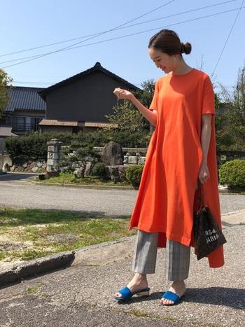 オレンジカラーのビッグシルエットのロングTシャツワンピースにキレイめのチェックパンツのスタイリング。カジュアルと上品のバランスが絶妙です。足元に鮮やかなブルーのサンダルを合わせて、補色のコントラストを楽しんで。