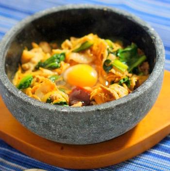 キムチがピリ辛なのはもちろん、ご飯にもコチュジャンを混ぜているので、スパイシーさを堪能できます。こちらは石鍋で作っていますが、お家に石鍋がない時はフライパンで少し焼き付けてから器に盛り付けると◎。