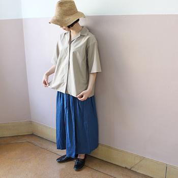 ゆったりめの開襟シャツに、空色のフレアスカートをカップリング。あえてウエストインはせず、くつろぎ感のあるエアリーラインを楽しんで。帽子はつば広にし、無駄のないコーディネートにアクセントをプラス!