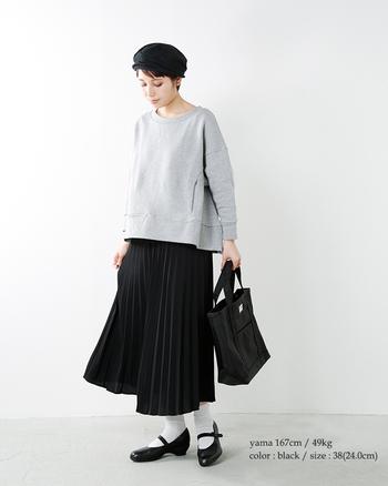 黒のプリーツスカートにスウェットを合わせたミックスコーディネート。足元はストラップシューズでかわいらしさをプラス。