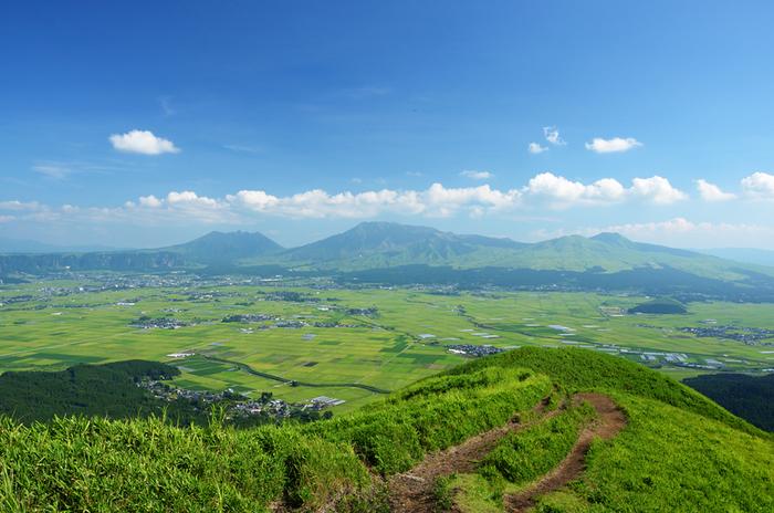 """阿蘇外輪山の最高峰約936mの「大観峰」は、阿蘇カルデラや阿蘇五岳、九重連山…360度どこを見渡しても雄大な風景が広がり、ダイナミックな自然を感じるには絶好のロケーション。ちょうど正面に見える阿蘇五岳がお釈迦様が寝ているように見えるため""""涅槃像""""と呼ばれています。眺めているだけで、なんだか運気もアップしそうですね!"""