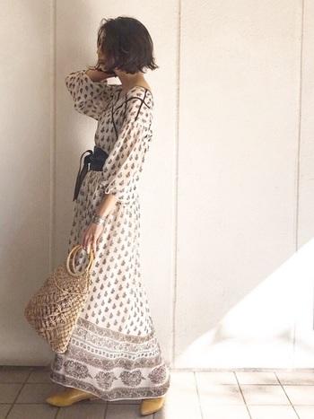 ヴィンテージ風のエスニックプリントのマキシ丈ドレスは、サッシュベルトを使ってスタイルアップ。透け感のあるカゴバッグとマスタードイエローのフラットシューズが女性らしい、大人リラックなスサマースタイルです。