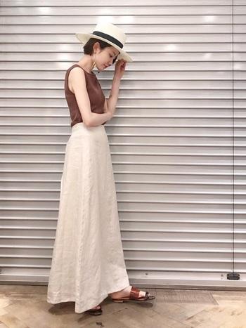 縦長Iラインの大人っぽいロングスカートスタイルに、直線的な白いストローハットがピリッとクールなアクセントを加えています。アースカラーとホワイトの組み合わせは、上品な大人の装いを演出します。