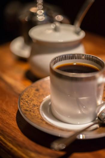 画像は湯せんによって温める『水出しコーヒー こいめ』。  冷たい「水出し珈琲(濃いめ)(アイス)」にもノリタケのカップが使われています。風味を尊重するため、氷は入れません。