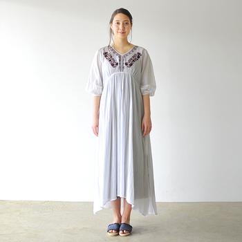 胸元の刺繍がボヘミアンなマキシ丈ワンピース。アシンメトリーな裾がニュアンスを作り、フラットサンダルの足元をきれいに見せてくれます。
