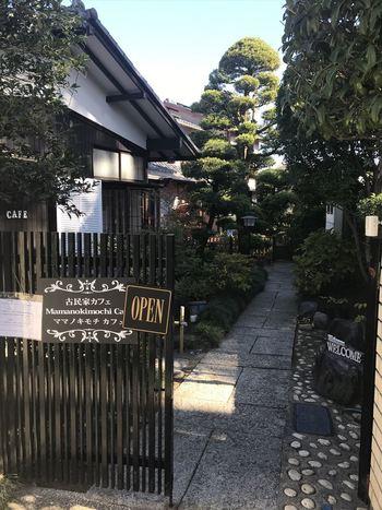 京成本線の「菅野」駅を出て線路沿いに3~4分ほど歩いた一軒屋カフェ「Mamanokimochi Cafe (ママノキモチカフェ)」。閑静な住宅街にあり、大きな木や石畳のエントランスなど趣きのある建物です。